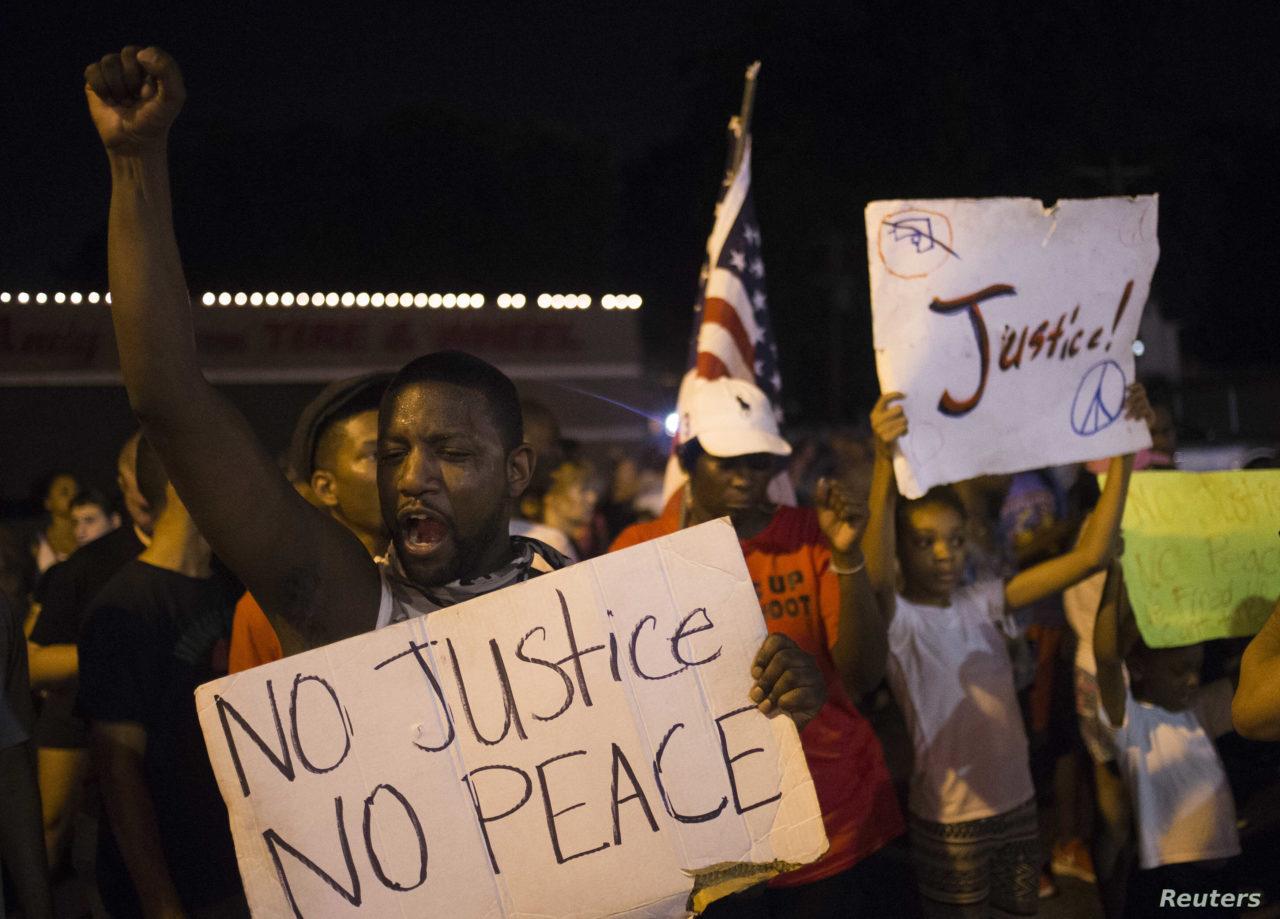 Demonstrators protest the killing of unarmed teen Michael Brown across the street from the Ferguson Police Department  in Ferguson, Missouri